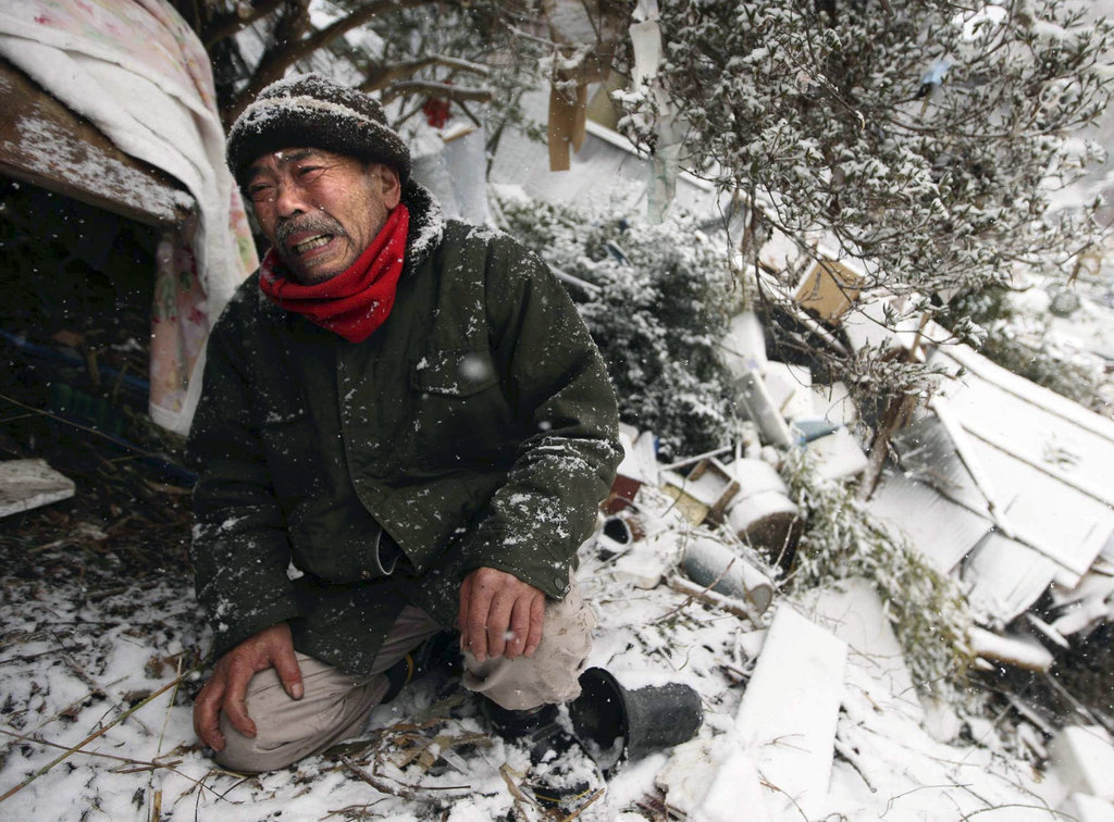 A man grieves in front of te wreckage where his mother's body was buried.